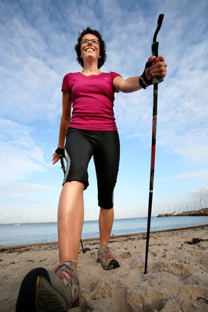 woman training nordic walking on a beach in denmark photo