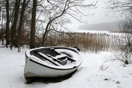 冬にデンマークでアイス湖でボートします。 写真素材