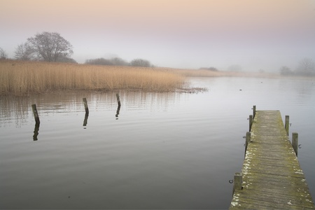 a lake in denmark in the winter time with a foggy weather