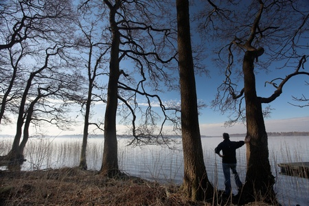 Man at  a lake in denmark nearby a forest, water and trees Stock Photo - 9742230