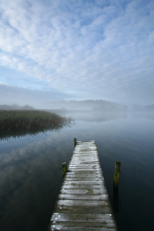 A lake in denmark , a so called bath bridge with fog and nice sky photo