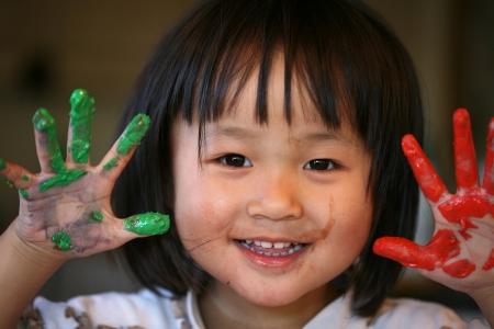 ni�os chinos: cerca de la cara de ni�o jugando con pintura de dedo Foto de archivo