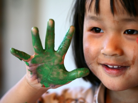 close up of  child face playing with finger painting