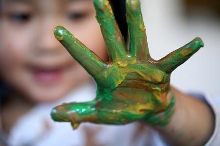 ni�os pintando: cerca de la cara de ni�o jugando con pintura de dedo Foto de archivo