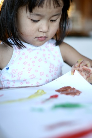 child painting and playing with colours (chinese child) photo