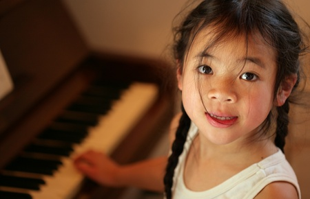 child profile  looking in fthe camera while playing piano