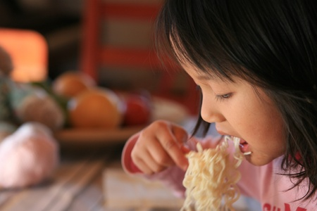 close up of hungry child eating pasta photo