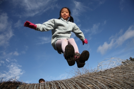 happy child outdoor jumping a summer day against a blue sky photo