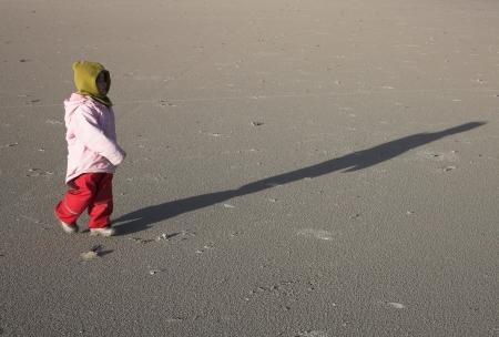 gladden: small girl running on a beach in denmark in winter
