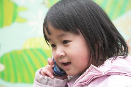heureux vocation extérieure de l'enfant sur un téléphone contre un mur décoré