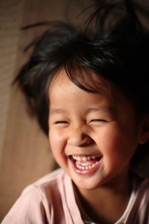 près de la tête de l'enfant tout en riant