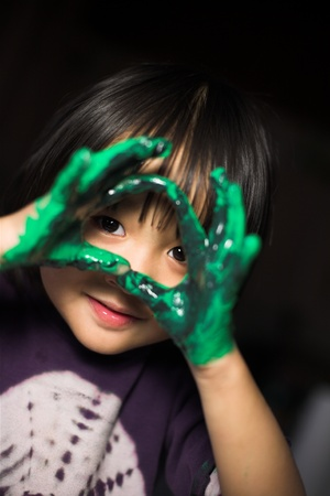 plenitude: close up of  child face playing with finger painting