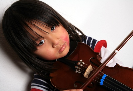 Cute child looking at the camera with a violin in hands photo