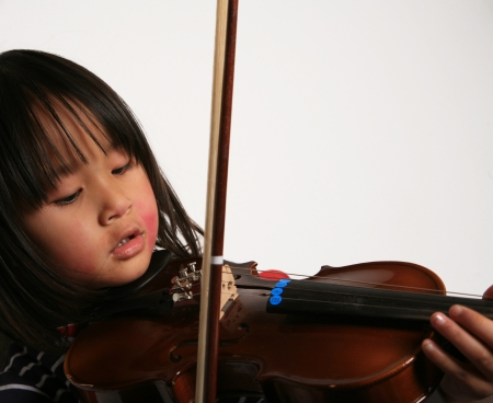 Cute child looking at the camera with a violin in hands Imagens