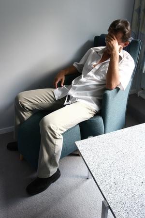 絶望的な疲れている男の頭の上の手で椅子に