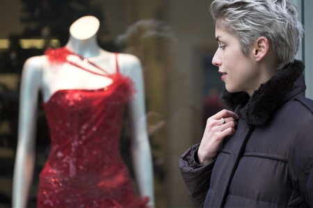 woman outdoor in a city on shopping tour, looking into a shop window photo