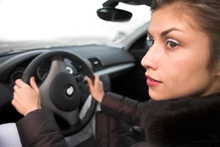 jolie femme conduire une voiture les mains sur le volant, en regardant sur le côté gauche
