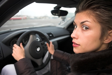 pretty woman driving a car hands on the wheel, looking at left side photo