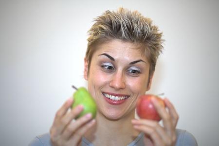 hesitating: mujer vacila: sosteniendo una pera y una manzana