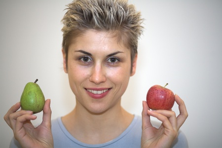 hesitating: woman hesitating : holding a pear and  an apple  Stock Photo