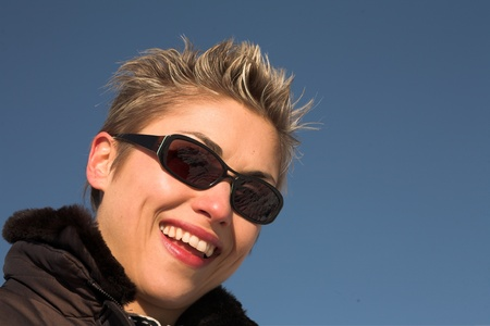 hilarity: happy woman outdoor in winter shot against a blue sky in the sun Stock Photo