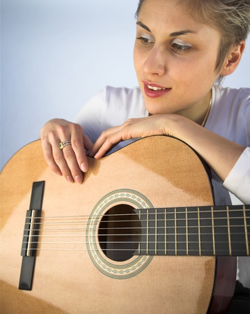 plenitude: Blond short hair woman woman with white Tshirt playing acoustic guitar Stock Photo