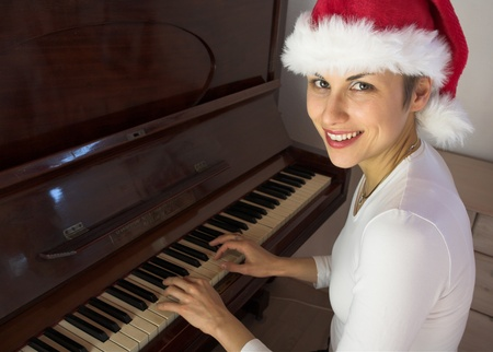 ivories: Blond short hair woman woman with white Tshirt playing piano with a santa hat Stock Photo