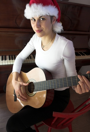 Blond sj´hort hair woman woman with white Tshirt playing acoustic guitar with santa hat photo