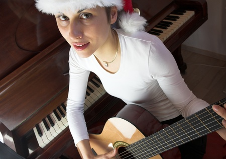 Blond sj�hort hair woman woman with white Tshirt playing acoustic guitar with santa hat photo