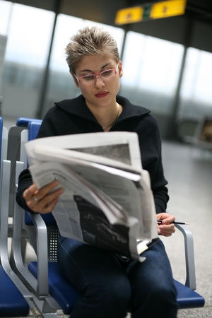 pretty woman reading a newspaper Stock Photo - 10071371
