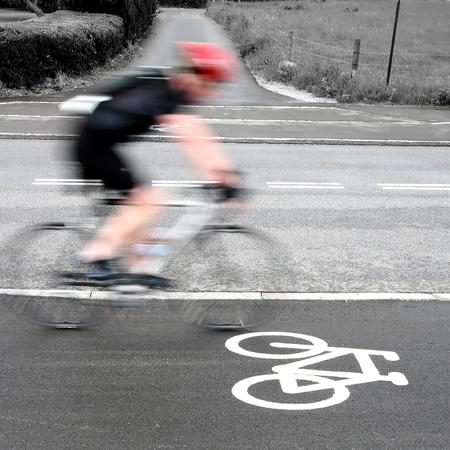 wielerwedstrijd in Denemarken, worden fietser langs een fiets teken op de weg. Geschoten met een lage sluitertijd om bewegingsonscherpte te bereiken Stockfoto