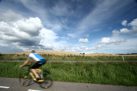 summer sky with nice cloud formation / cyclist passing by Stock Photo - 11752338