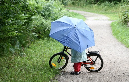 child on  a bicycle with a blue umbrella photo