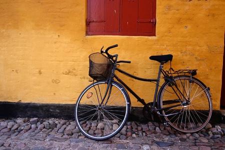 自転車、黄色の壁、夏でグレーノーのデンマークの村の通り