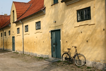 holidays vacancy: Large yellow l house   a sunny summer day with a bike  in a village in denmark