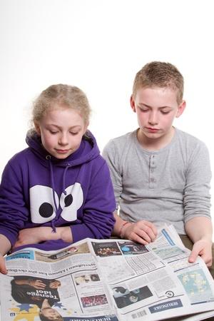 reading newspaper: child reading newspaper Editorial
