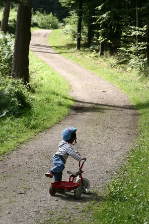 child on cycle on a path in the countryside  in denmark