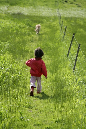 small girl running in a green field in spring photo
