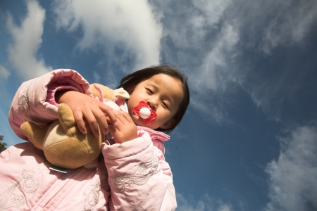 close up of  child face with pacifier in mouth photo