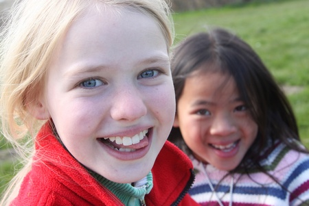 gladden: Close up of face of happy children while smiling laughing and playing together