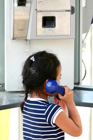 jeune enfant dans une cabine téléphonique en France Banque d'images