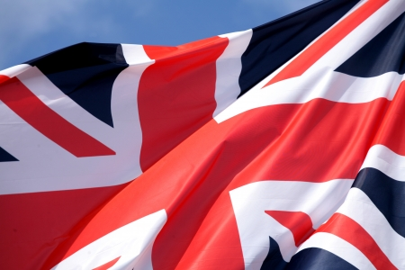 symbolization: UK flag in the wind and sun with gray sky Stock Photo