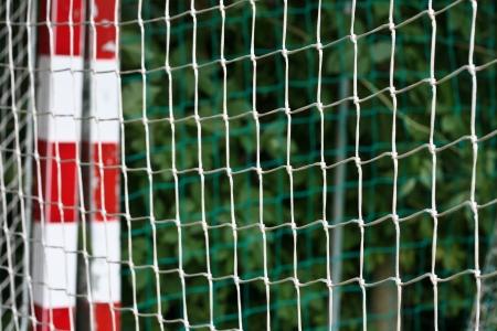 détail d'un but de handball avec des rayures rouges et blanches