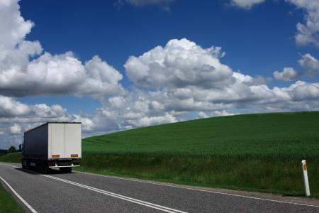 METEO champ de céréales au Danemark en été. Camion passant par près de vieilles voitures anciennes collection signes de circulation dans une ville près de vieilles voitures anciennes collection