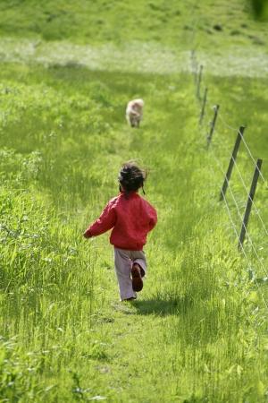gladden: small girl running in a green field in spring