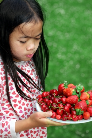 plenitude: child holding a plate of cherry and strawberries on green background