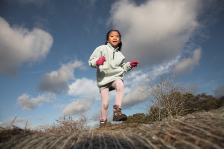 plenitude: happy child outdoor jumping a summer day  against a blue sky