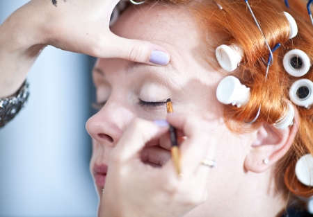 red haired girl: Make up artist at work on a red haired girl