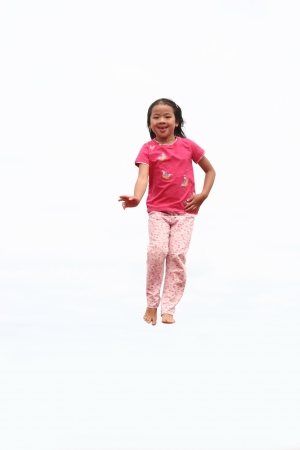 plenitude: happy child outdoor jumping a summer day against a white sky Stock Photo