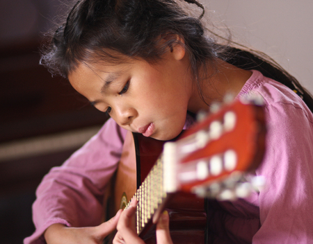 girl playing guitar: Cute girl playing guitar indoor with high concentration